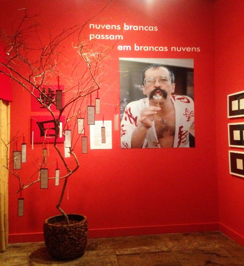 Ao lado da imagem de Paulo Leminski, Alice Ruiz recebeo público na entrada da exposição.