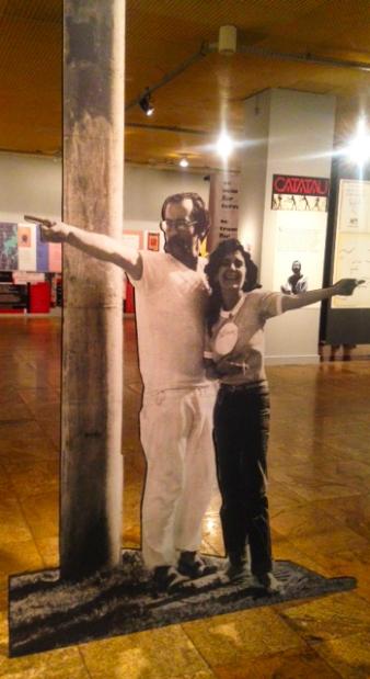 imagens de Paulo Leminski e Alice Ruiz recebendo público na entrada da exposição.