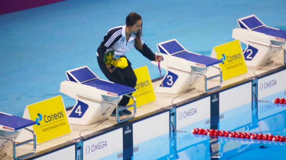 Larissa MArtins Oliveira realiza ritual comum entre nadadores. molhar a medalha na agua da piscina